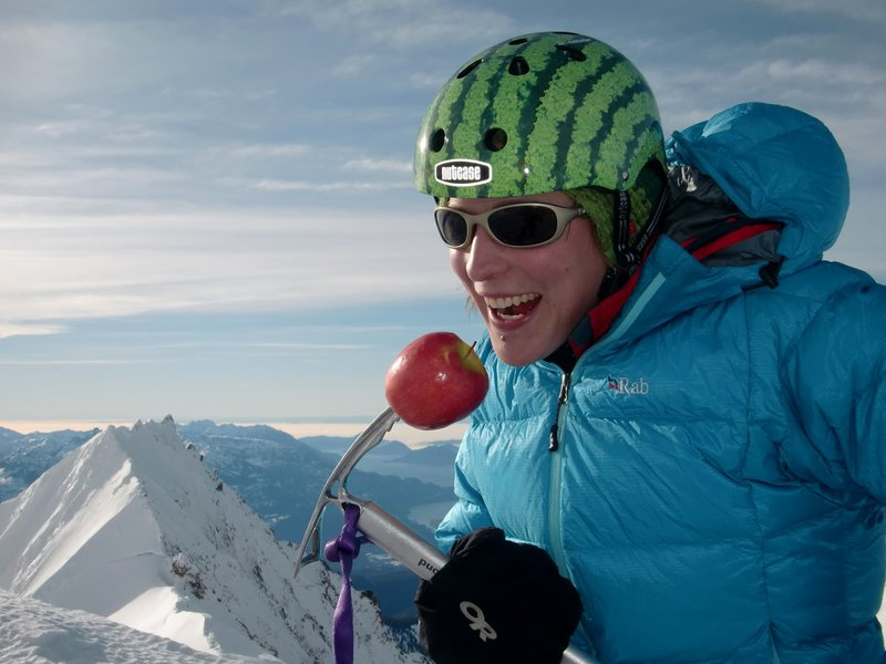 Natalie Stafl and summit apple on the peak of Garibaldi Mountain. Photo: Nick Matwyuk