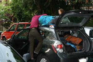 Caroline strapping Jim's pack to Natalie's car.