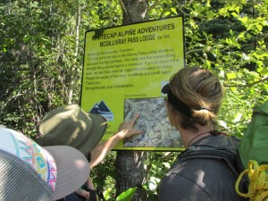 """Alex and Elliott are debating whether or not to believe the """"You Are Here"""" marker on this erroneous map at the start of the logging road"""