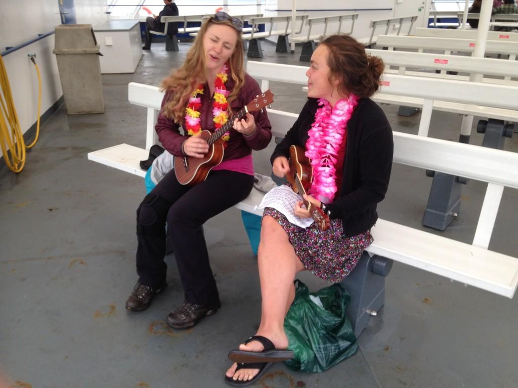 Cora and Roseanna playing ukulele on ferry over. Photo by Jake Jones.