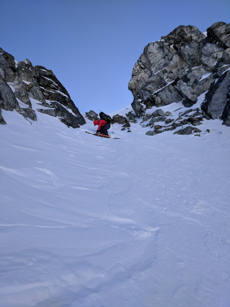 Olek putting on his skis at the rocky entrance to the Eureka NW couloir.