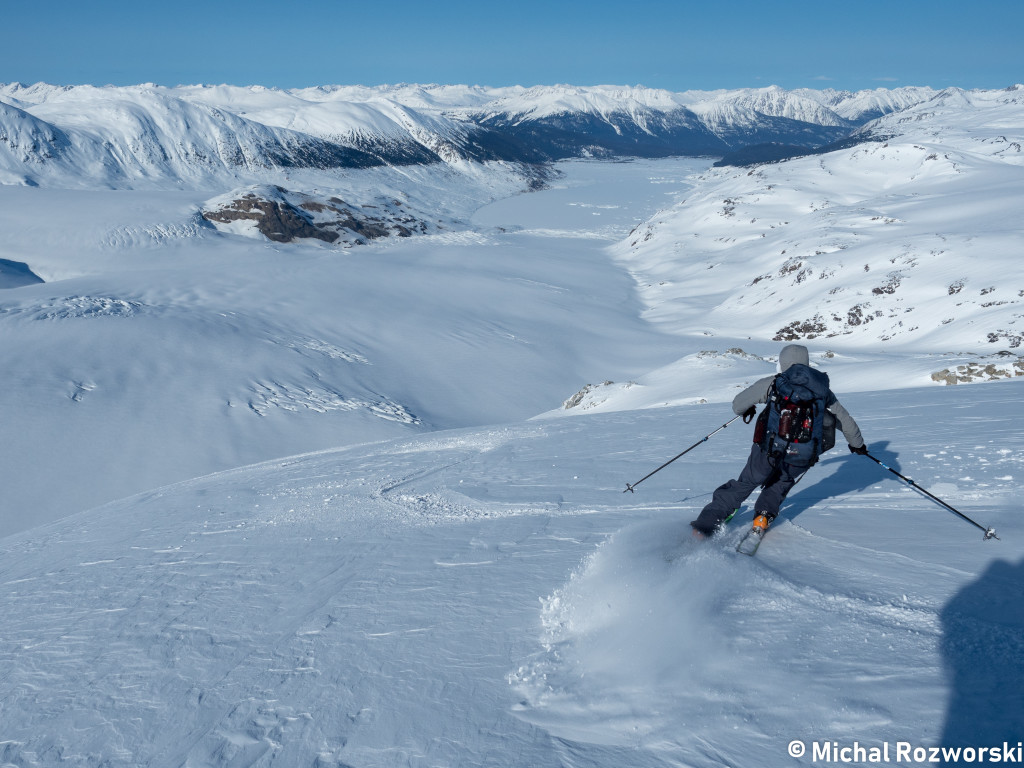 Olek skiing down the Bridge Glacier and Camp 2; the lake at the end of the glacier is recent climate change creation.