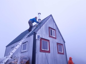 Cassandra slowly making her way on to the roof to fix the chimney cap.