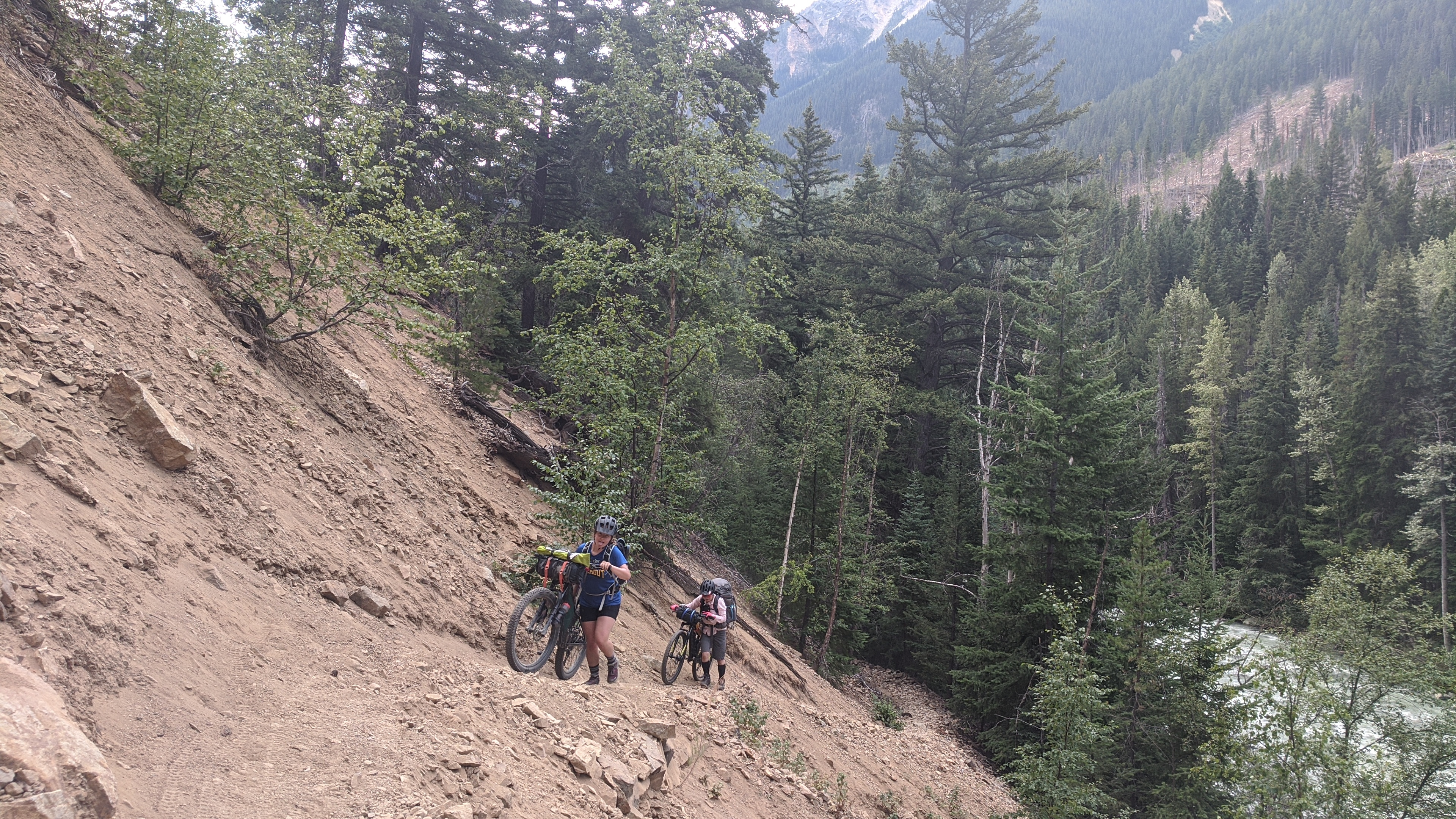 Melissa and Shuyu hike-a-bike on the washed-out scree slope